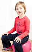 Retrato de muchacha sentada sobre una pelota — Foto de Stock