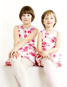 Portrait of two sisters wearing similar dresses — Stock Photo