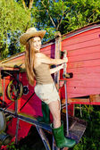Young woman standing by old threshing machine — Stock Photo