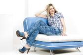 坐在沙发上穿着牛仔裤和牛仔木屐的女人 — 图库照片