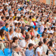 The audience in the stands at a football match - Stock Photo