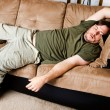 A guy flung all over the couch — Stock Photo #12122706