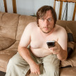Young man sitting on the couch working the TV — Stock Photo