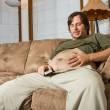 Heavy set man on the couch admiring his stomach — Stock Photo