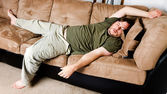 A guy flung all over the couch — Stock Photo