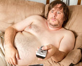 Fat lazy guy watching the TV — Zdjęcie stockowe