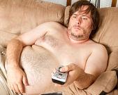 Fet lat kille tittar på tv: n — Stockfoto