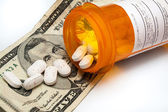 Bottle of prescription pills laying on money — Stock Photo