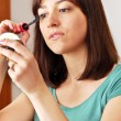 Young woman applying makeup — Stockfoto