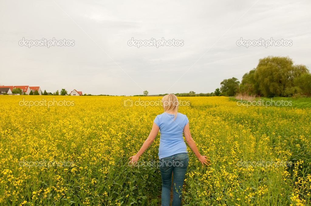 Thoughtful young woman in rape field — Stock Photo #11161907