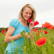 Royalty-Free Stock Photo: Woman smelling a poppy