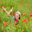 Woman lying in a poppy field — Stock Photo
