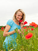 Woman smelling a poppy — Stock Photo