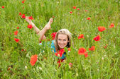 Woman lying in a poppy field — Stockfoto
