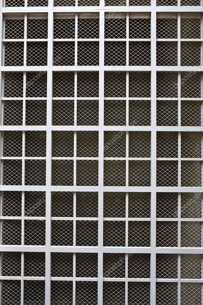 Dull silver color metal bars over screen covering building window — Stock Photo #11136158