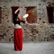 Stock Photo: Young Girl Twisting Burning Poi