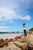Portrait of a young man standing on a beach with a camera — Stock Photo