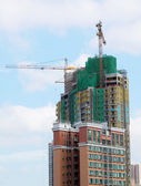 Building crane and building under construction against blue sky — Stock Photo