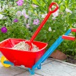 Garden wheelbarrow with sand - Stock Photo