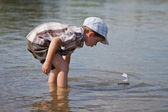 Boy launches a small sailboat — Stock Photo