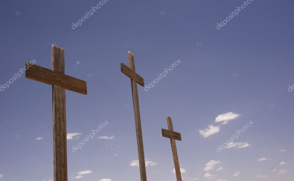 Three wooden crosses stand against blue sky  Stock Photo #10789006
