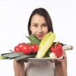Young woman holding a plate with fresh vegetables — Stock Photo