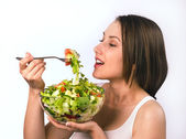 Young woman eating healthy salad — Stock Photo