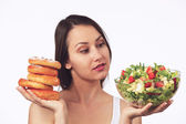 Dilemma: Sweet cakes or healthy salad? — Stock Photo