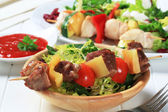 Grilled pork skewer and spring salad — Stock Photo