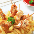 Chicken pieces on sticks and French fries — Stock Photo