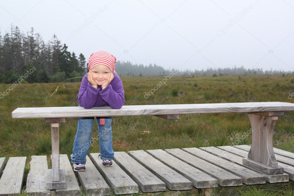 Little girl resting on a bench while hiking at torfhaus highmoor, lower saxony, germany — Stock Photo #11610876
