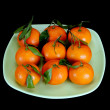 Stock Photo: Tangerines on a plate on a black background