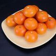 Tangerines on a plate on a black background — Stock Photo