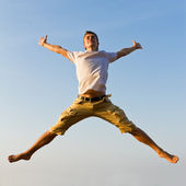 Happy young man jumping against blue sky background — Stock Photo