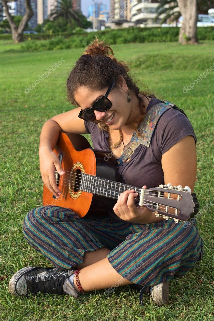 Beautiful smiling young Peruvian woman playing the guitar in a park (Selective Focus, Focus on the face of the woman) — Stock Photo #10932402