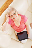 Smiling woman at home holding tablet PC — Stock Photo