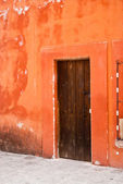 Orange adobe house with wood door — Stock Photo