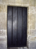 石の壁の黒いドア — ストック写真
