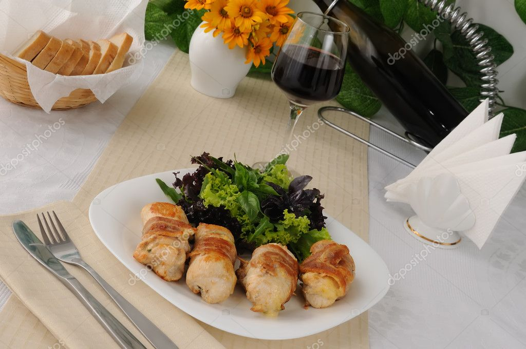 Chicken rolls stuffed with cheese, wrapped in bacon and herbs in a tomato-garlic sauce — Stockfoto #10894706