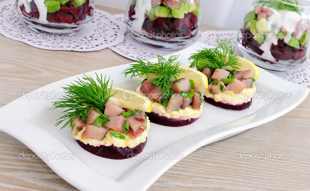 Appetizer of herring with onions on the beets and eggs, lemon and dill — Stock Photo #11424824