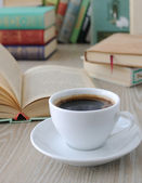 Cup of coffee on a table with books — Stok fotoğraf