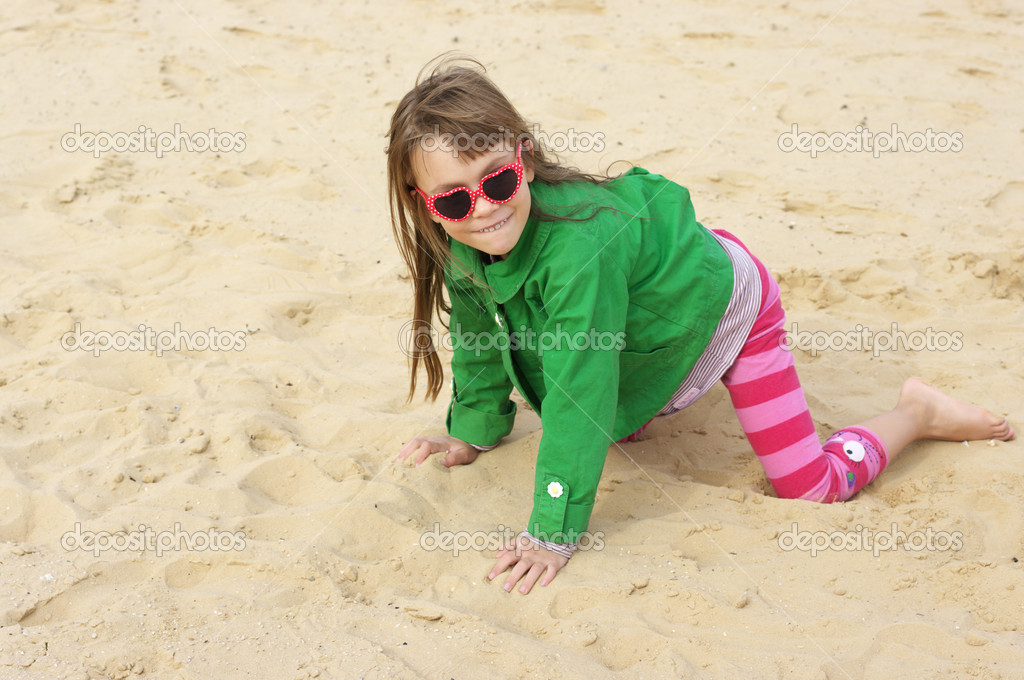 Small cute girl playing on sand at beach. — Stock Photo #11069856