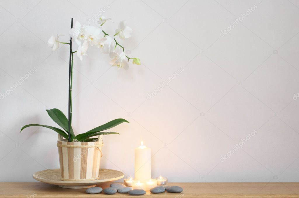 Orchid in pot, candles and stones on table against light wall. — Stock Photo #11422027