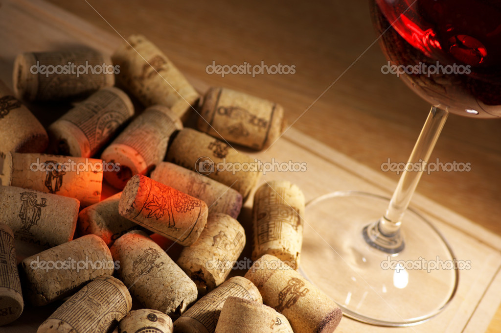 Heap of used vintage corks with glass of red wine and reflex. — Stock Photo #11617040