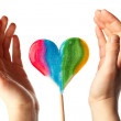 Hands surrounding lollipop heart — Stock Photo