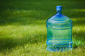 Water big bottle on green grass background — Stock Photo