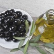 A plate with black olives and oil. - Foto Stock