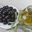 A plate with black olives and oil. - Stock Photo