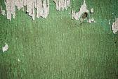 Escamas de pintura verde sobre fondo de madera descolorida — Foto de Stock