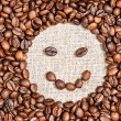 Coffee beans happy smile on burlap — Stock Photo